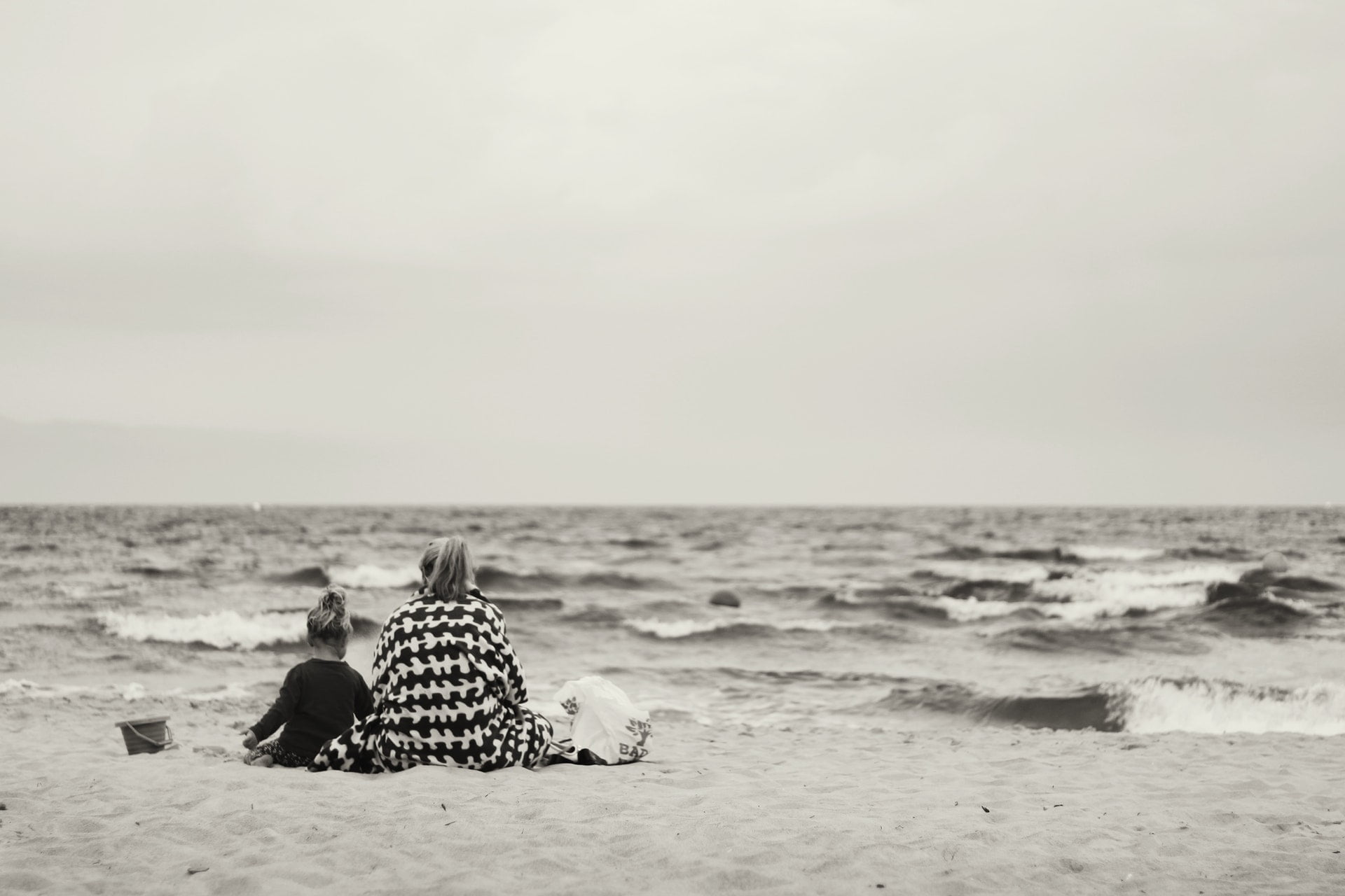 woman and child sitting on sand near body of water mother ocean 1 離|藍雀一行詩