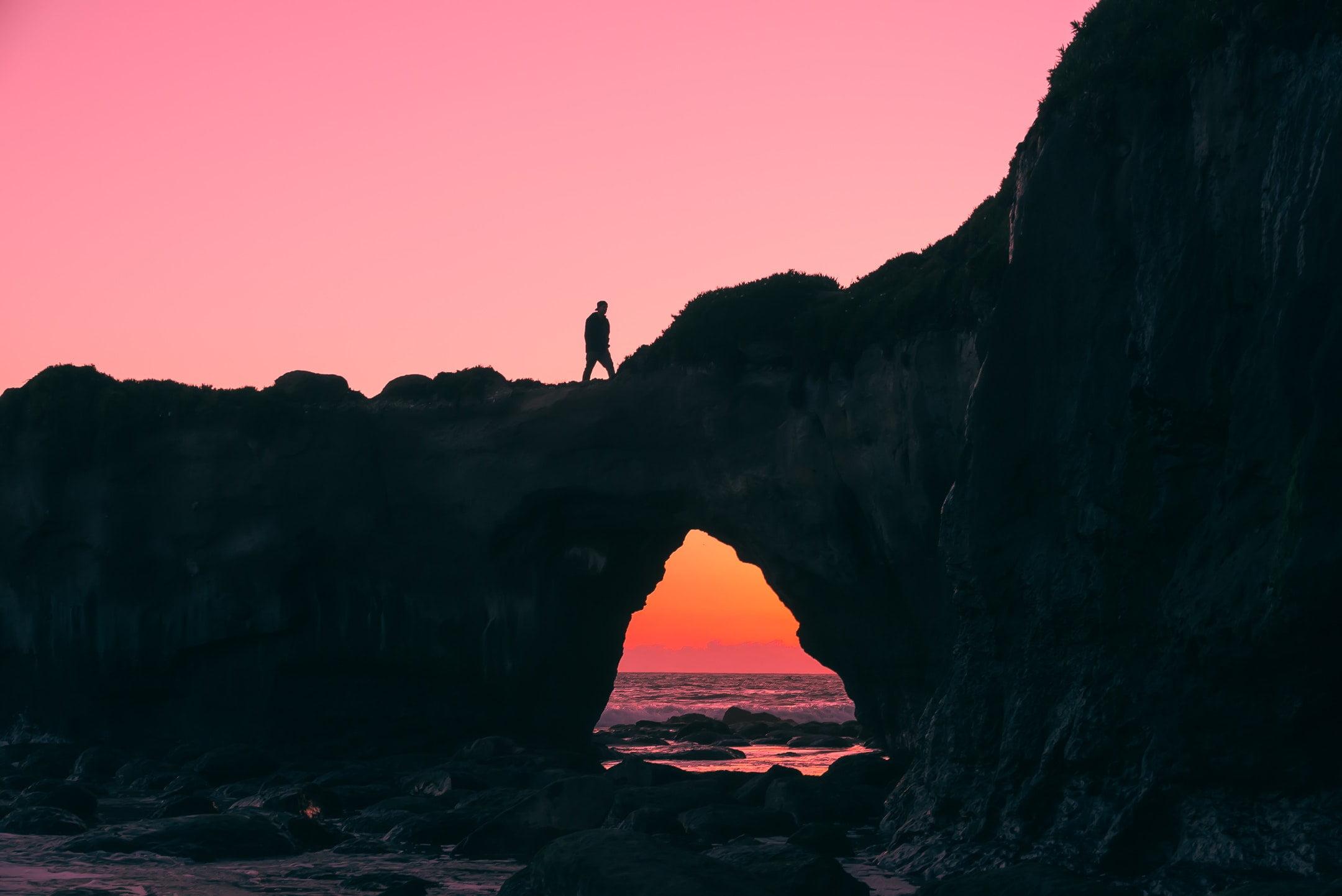 man on rock walking during nightime sunset sea bridge 國民自焚丨玄明詩選